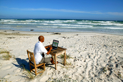 Bald man working at his desk on the beach